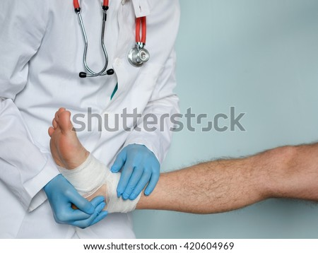 close up of doctor bandaging one injured foot after an accident - stock photo