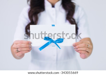 Close up of doctor holding blank white gift card - stock photo