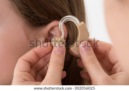 Close-up Of Doctor Inserting Hearing Aid In The Ear Of A Girl - stock photo