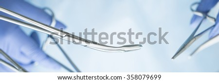 Close-up of doctor's hands holding surgical clamps. Medical background. Letter box format - stock photo