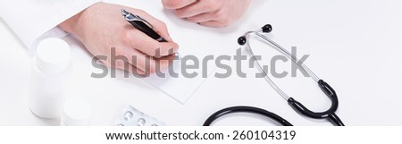 Close-up of doctor's hands writing out a prescription - stock photo