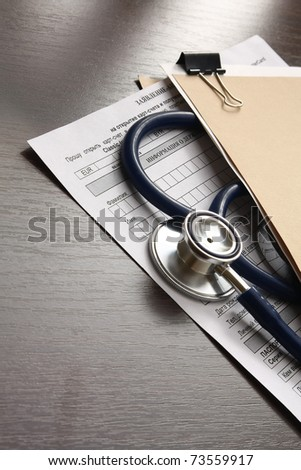 Close up of doctor's stethoscope and patient's medical information. - stock photo