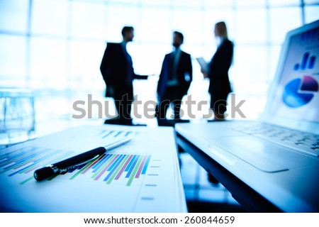 Close-up of document with pen and laptop in office - stock photo