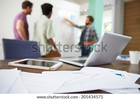 Close Up Of Documents And Laptop With Meeting In Background - stock photo