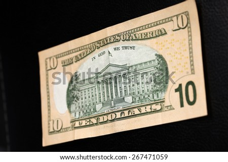 close-up of 10-dollar bills on black leather background studio - stock photo