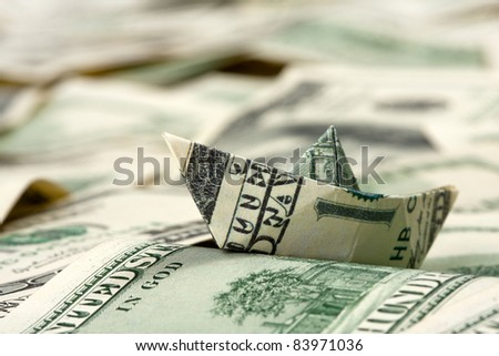 Close-up of dollar boat swimming in financial sea - stock photo
