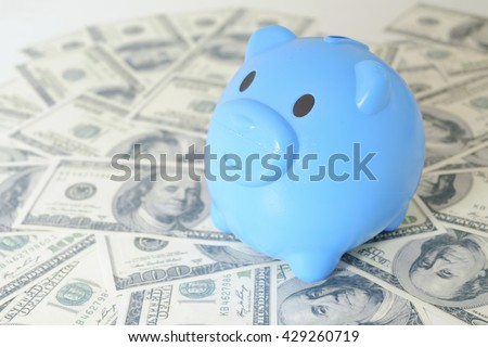close up of dollar cash money and piggy bank on table. business, finance, investment, saving and corruption concept - stock photo