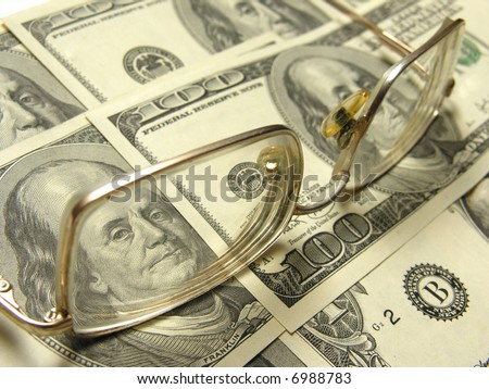 close-up of dollars and eyeglasses