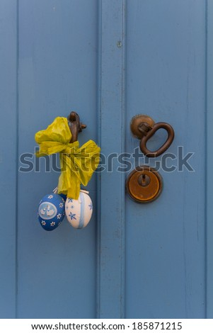 Close up of door handle with Easter decoration with an old wooden door paired blue - stock photo
