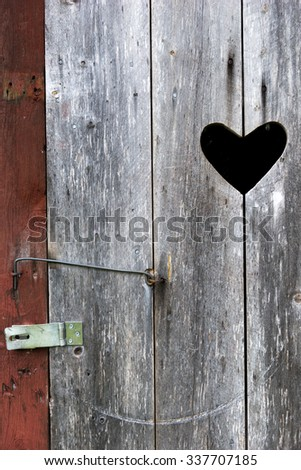 Close up of door with heart on old wooden outdoor traditional Swedish toilet in countryside - stock photo