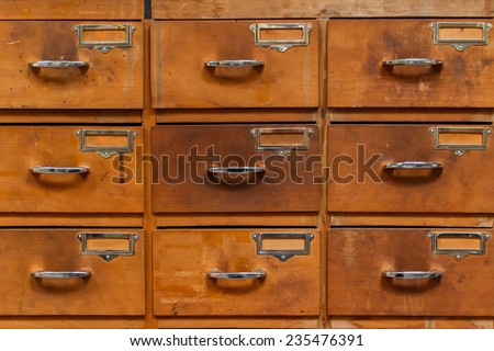 Close-up of drawers with blank tags in vintage furniture module - stock photo