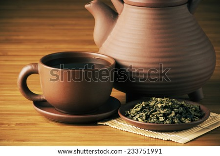 Close-up of dried tea, cup of tea and teapot on wooden background. - stock photo