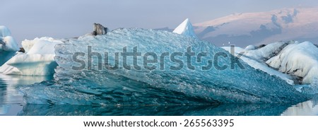 Close up of drifting ice fragment in panorama of Jokulsarlon glacier lagoon, Iceland. - stock photo