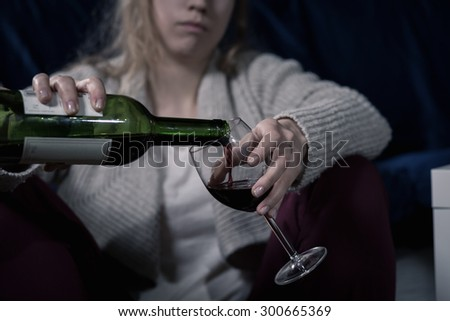 Close-up of drunk woman pouring glass of red wine - stock photo