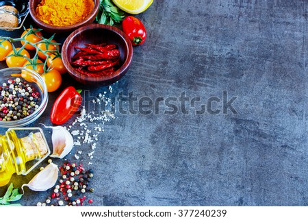 Close up of dry colorful spices in bowls with fresh seasoning and healthy vegetables on dark rustic background, selective focus, border. Vegetarian or diet food concept