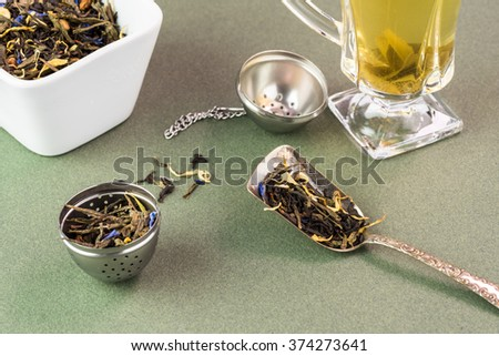 Close up of dry green tea on a spoon and in a solid teaball.