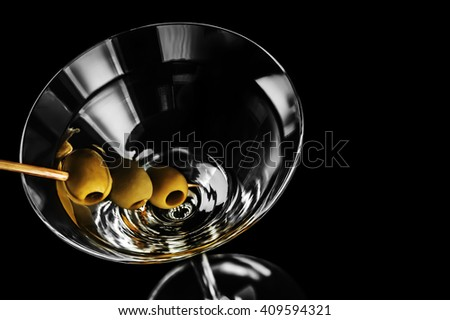 Close-up of dry martini with green olives on black background - stock photo
