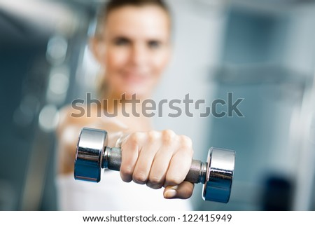 close-up of dumbbell, a young woman is holding at arm's length - stock photo