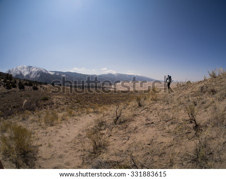 Close up of dune with backpacker walking away shows Path along grassy area with pristine dunes in background, and snowy mountains behind that  Taken at Great Sand Dunes National Park in Colorado - stock photo