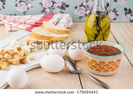 Close up of eggs, marinara sauce, baked cubes of bread - ingredients for shirred eggs with marinara and feta.