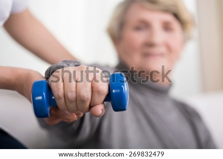 Close-up of elder woman training with physiotherapist - stock photo