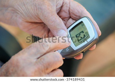 Close up of elderly man's hands measuring his blood sugar with a blood sugar monitor. This is six of a six picture series. In this picture he reads the result of the blood sugar test. - stock photo