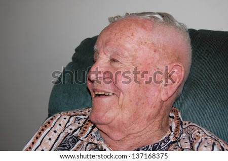Close up of elderly man smiling to side. - stock photo
