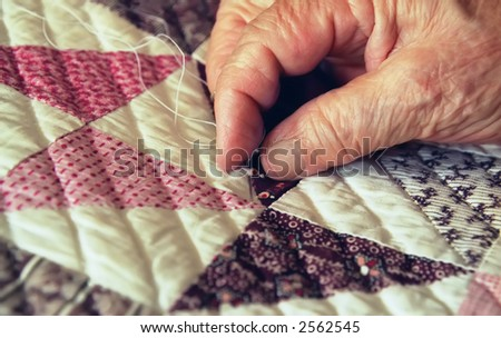 Close-up of Elderly Woman's Hand Busy Quilting - stock photo