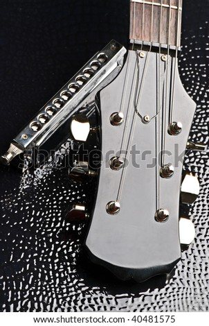 close-up of electric guitar headstock and harmonica - stock photo
