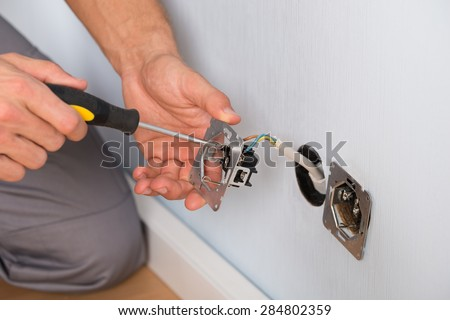 Close-up Of Electrician Hands With Screwdriver Installing Wall Socket - stock photo