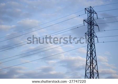 close up of electricity pylon against blue cloudy sky