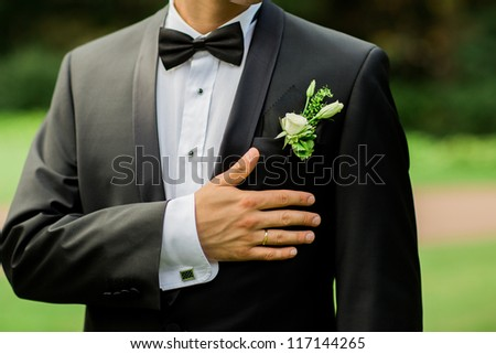 Close-up of elegance groom hands with ring, and cufflink