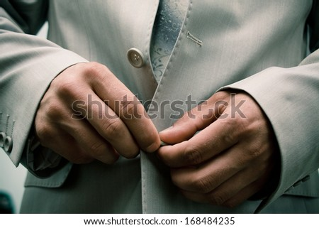 Close-up of elegance man hands with necktie