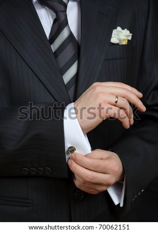 Close-up of elegance man hands with ring, necktie and cufflink