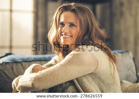 Close-up of elegant, smiling brunette woman, hugging her knees. Dressed casually, she is relaxing. Retro chic ambiance and cozy atmosphere. - stock photo
