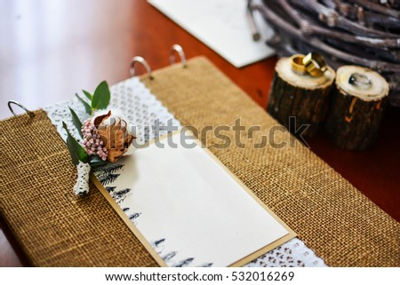 Close up of elements of wedding decor photo album wood with rings and twig cotton.