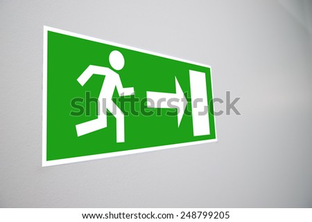 Close-up Of Emergency Evacuation Sign On Wall - stock photo