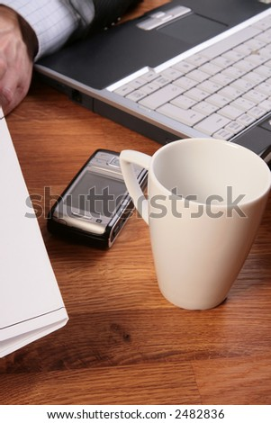 Close-up of empty coffee mug in office setting. Focus on cup with laptop, mobile phone and hand slightly out of focus.