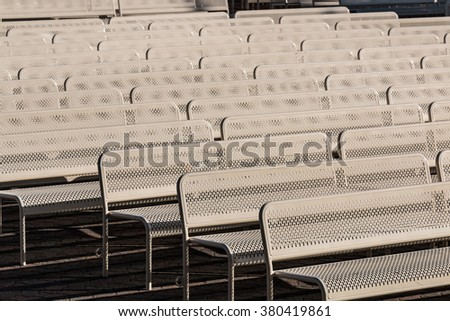 Close-up of empty outdoor audience benches in rows facing right. - stock photo