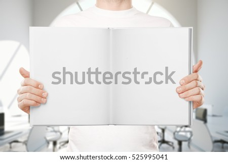 Close up of empty white book in man's hands. Mock up