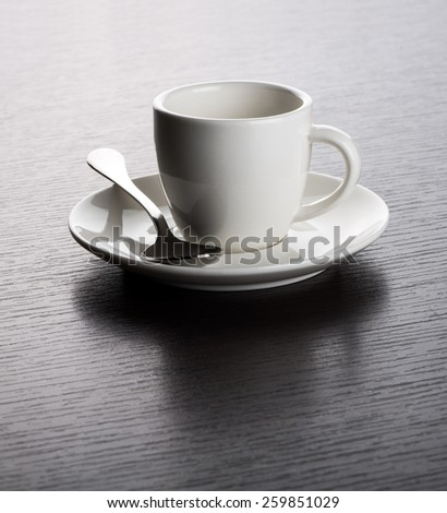 Close Up of Empty White Mug on Saucer with Silver Spoon on Dark Wooden Table with Visible Wood Grain - stock photo