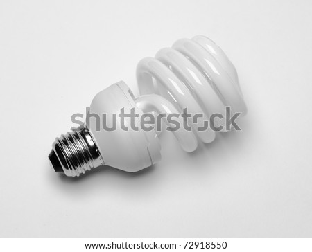 close-up of energy saving compact fluorescent light bulb with shadow on white background - stock photo