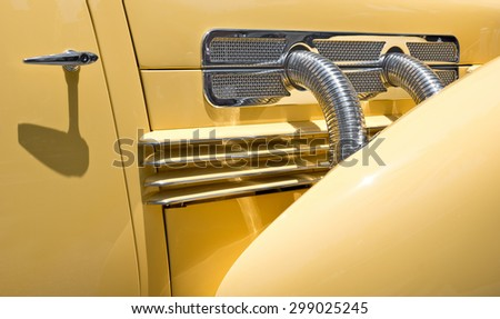 Close up of engine pipes on a vintage vehicle and door handle.  - stock photo