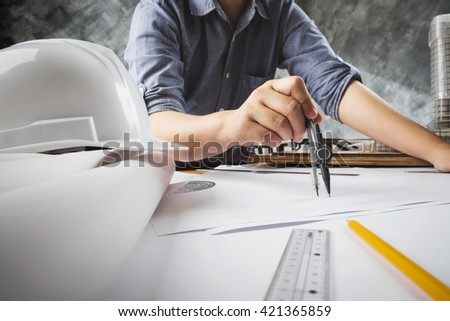 Close up of engineer hand sketching a construction project with Pencil, compass. - stock photo