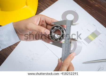 Close up of engineer to measuring bearing by vernier caliper - stock photo