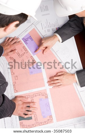 Close-up of engineers looking at blueprints with sketches of projects - stock photo