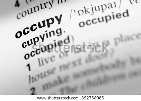 Close up of English dictionary page with word occupy