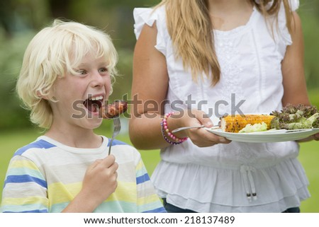 Close up of enthusiastic boy taking a bite of barbecued sausage - stock photo