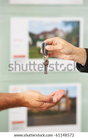 Close Up Of Estate Handing Over Keys Of New Home To Client - stock photo