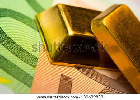 Close-up of euro banknotes and two gold ingots - stock photo